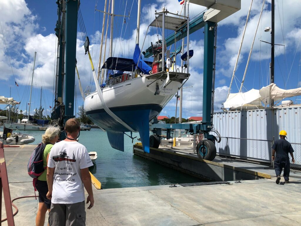 Owner watches while his sail boat is lifted